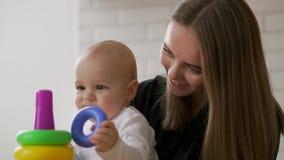 Weinig kindjongen en zijn mama spelen thuis met speelgoed stock video