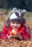 Weinig kindjongen met de appel in openlucht herfst stock foto