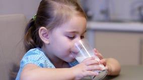 Weinig kindmeisje die een melk drinken stock videobeelden