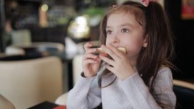 Weinig kindmeisje die kauwend een stuk van pizza met het uitrekken van kaas eten stock video