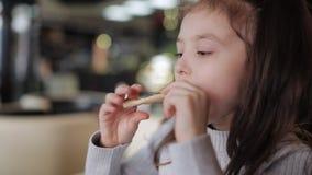 Weinig kindmeisje die kauwend een stuk van pizza met het uitrekken van kaas eten Close-up stock videobeelden