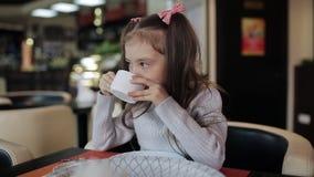 Weinig kindmeisje die kauwend een stuk van pizza met het uitrekken van kaas eten De baby eet ongezond voedsel stock video