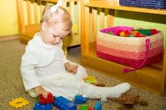 Weinig kindmeisje die in kleuterschool in de peuterklasse van Montessori spelen Aanbiddelijk jong geitje in kinderdagverblijfruim stock foto's
