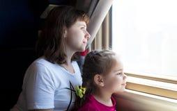 Weinig kindmeisje en haar moeder die door het venster aan de gang kijken stock foto