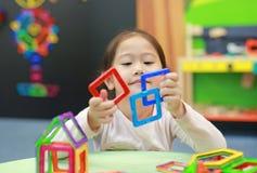 Weinig kindmeisje het spelen Magnetenstuk speelgoed voor hersenenontwikkeling stock foto's
