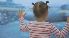 Weinig kindmeisje kijkt uit venster op vliegtuig, achtergedeelte wiew stock videobeelden