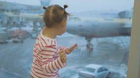 Weinig kindmeisje kijkt uit venster op vliegtuig en het dansen, achtergedeelte wiew stock video