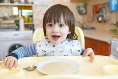Weinig kindtijd van 2 jaar eet tarwehavermoutpap met pompoen Stock Afbeelding
