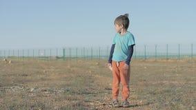 Weinig kindvluchteling met vuil op zijn kleren gebied van het vluchtelingskamp door een hoge omheining, slecht die de pluchekonij stock footage
