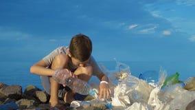 Weinig kindvrijwilliger die het strand schoonmaakt bij het overzees Veilig ecologieconcept stock footage