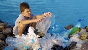Weinig kindvrijwilliger die het strand schoonmaakt bij het overzees Veilig ecologieconcept stock videobeelden