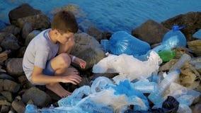 Weinig kindvrijwilliger die het strand schoonmaken bij de oceaan Veilig ecologieconcept stock footage