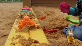 Weinig kindzitting in de zandbak en het spelen met vormen op de speelplaats stock footage
