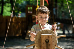 Weinig klimmer neemt de kabelbrug De jongen heeft prettijd, jong geitje die op zonnige warme de zomerdag beklimmen Stock Foto