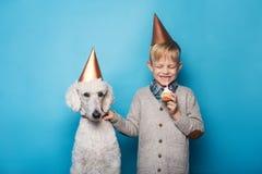 Weinig knappe jongen met hond viert verjaardag Vriendschap Liefde Cake met kaars Studioportret over blauwe achtergrond royalty-vrije stock afbeeldingen
