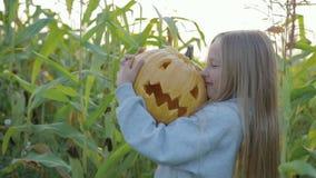 Weinig, koestert het mooie meisje en kust Jack ` s lantaarn vast, Halloween stock video