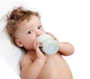 Weinig krullend-geleide baby zuigt een fles Stock Afbeeldingen