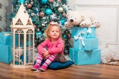 Weinig krullend glimlachend meisje die bijna Kerstboom bevinden zich Stock Fotografie