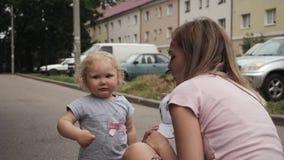 Weinig krullend-haired meisje met blauwe ogen spreekt aan haar moeder op straat het golven stock video
