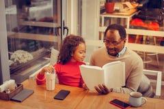 Weinig krullend meisje die aan haar boek van de vaderlezing voor haar luisteren stock fotografie