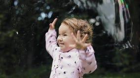 Weinig krullend meisje die in reusachtige bel gelukkig voelen Langzame Motie De bel toont stock videobeelden