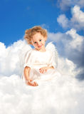 Weinig krullend meisje met feevleugels ligt op een wolk Stock Fotografie