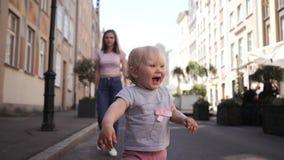 Weinig krullend meisjesblonde die met blauwe ogenreizen onderaan de straat van haar moeder het glimlachen lopen stock footage