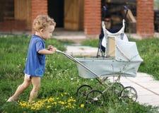 Weinig krullende jongen duwt een baby-vervoer Stock Foto's
