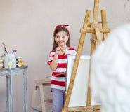 Weinig kunstenaarsmeisje die een penseel houden en over een canva kijken Royalty-vrije Stock Foto