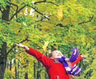 Weinig lachend mooi meisje in rode laag werpt gele bladeren in de herfstpark royalty-vrije stock fotografie