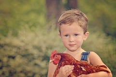 Weinig landbouwbedrijfjongen die rode kip houden Royalty-vrije Stock Afbeelding