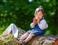 Weinig leuk babymeisje die fruit in bos eten Stock Fotografie