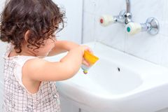 Weinig leuk babymeisje die haar tanden met tandenborstel in de badkamers schoonmaken stock afbeeldingen