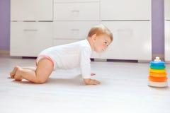 Weinig leuk babymeisje die leren te kruipen Gezond kind die in jonge geitjesruimte kruipen Glimlachend gelukkig gezond peutermeis stock foto