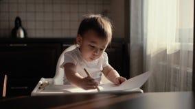 Weinig leuk babymeisje trekt een potlood op papier en verrast door haar werk stock footage