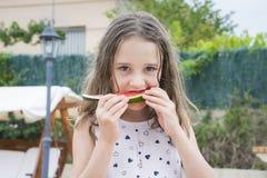 Weinig leuk blondemeisje die watermeloen eten Stock Afbeeldingen