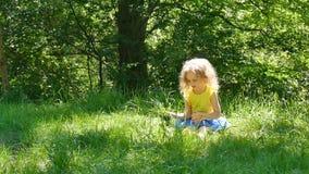 Weinig leuk blondemeisje in helder geel overhemd en blauwe rokzitting in het park op het groene gras en plukken omhoog het stock footage