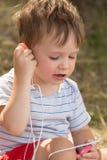 Weinig leuk jong geitje die aan muziek luisteren Stock Foto