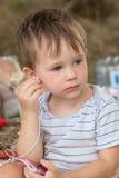 Weinig leuk jong geitje die aan muziek luisteren Stock Foto's
