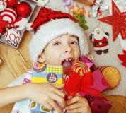 Weinig leuk jong geitje in santas rode hoed met met de hand gemaakte giften, de speelgoed uitstekende houten, warme winter Stock Foto