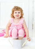 Weinig leuk krullend meisje in een roze kleding met stippen glimlachen, die op de witte stijl van de portiekprovence zitten Stock Fotografie