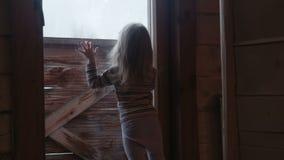 Weinig leuk meisje achter venster in de winter stock videobeelden
