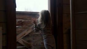 Weinig leuk meisje achter venster in de winter stock footage