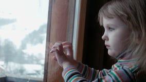 Weinig leuk meisje achter venster in de winter stock video