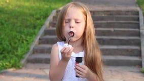 Weinig leuk meisje blaast bellen dichtbij treden in groen zonnig park stock video