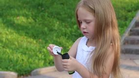 Weinig leuk meisje blaast bellen in groen zonnig park stock videobeelden