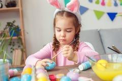 Weinig leuk meisje in de zitting van het de vieringsconcept van Pasen van konijntjesoren thuis het schilderen geconcentreerde pun stock afbeeldingen
