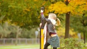 Weinig leuk meisje die bij de speelplaats in de herfst in openlucht spelen stock videobeelden