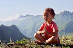 Weinig leuk meisje die bovenop berg mediteren Stock Afbeeldingen