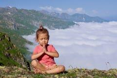 Weinig leuk meisje die bovenop berg mediteren Stock Fotografie